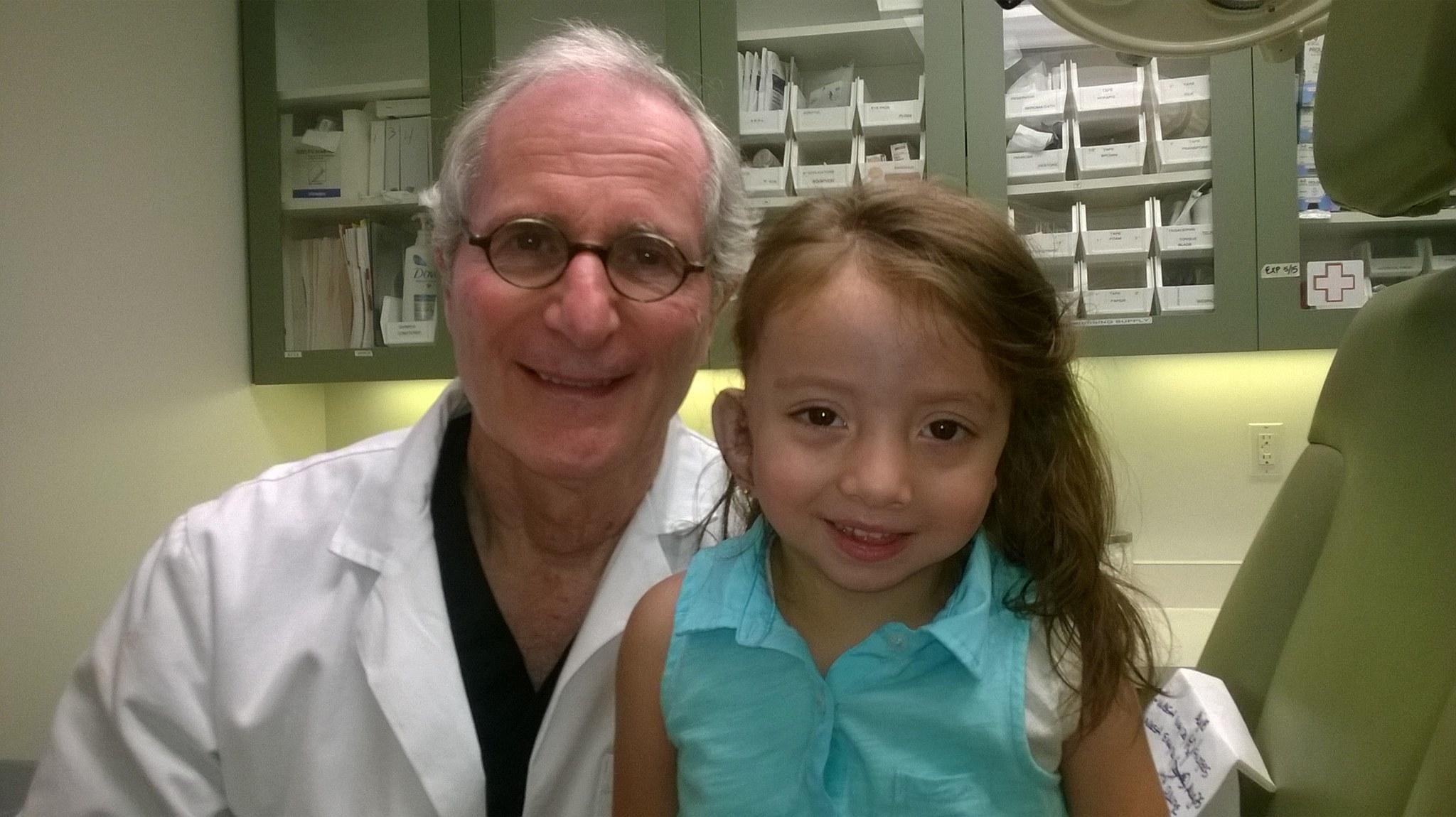 Belén con su doctor durante la primera cirugía de reconstrucción de orejas.